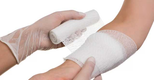 picture of someone applying a dressing onto a womens arm for basic wound care